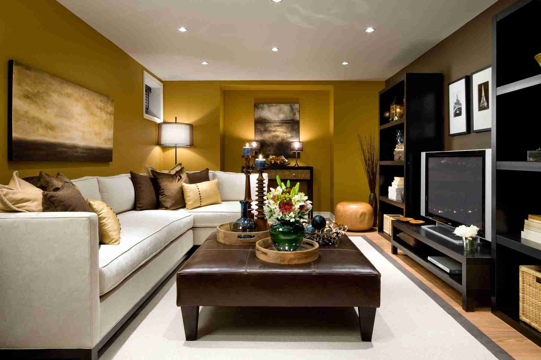 Yellow wall paint in the small living room with leather upholstered coffee table and angular gray sofa