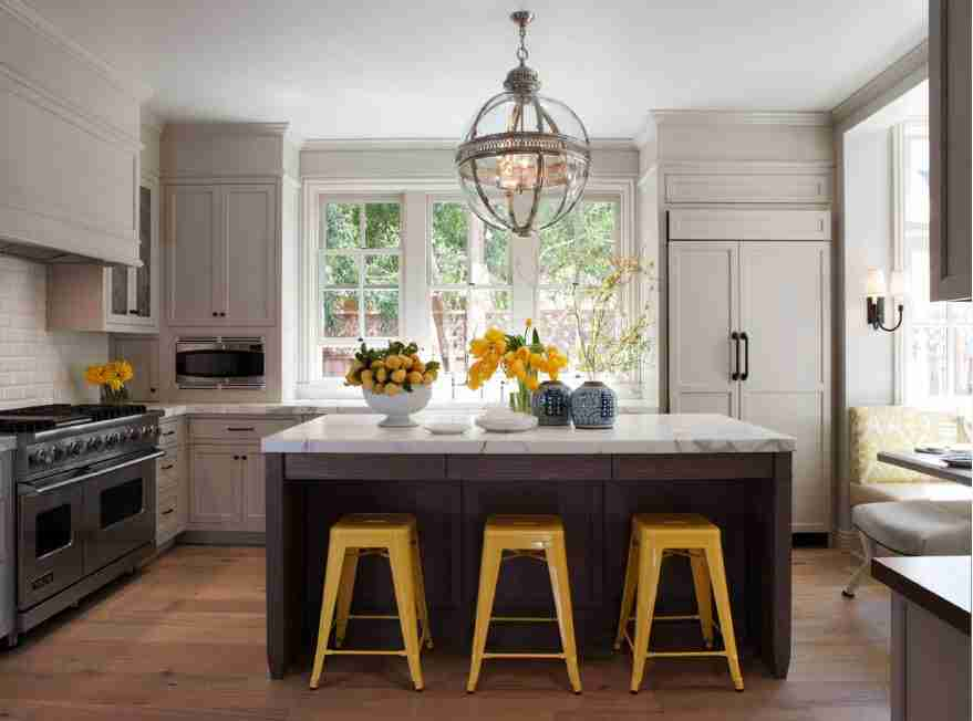 Yellow low chairs in the classic set kitchen with large island dark island