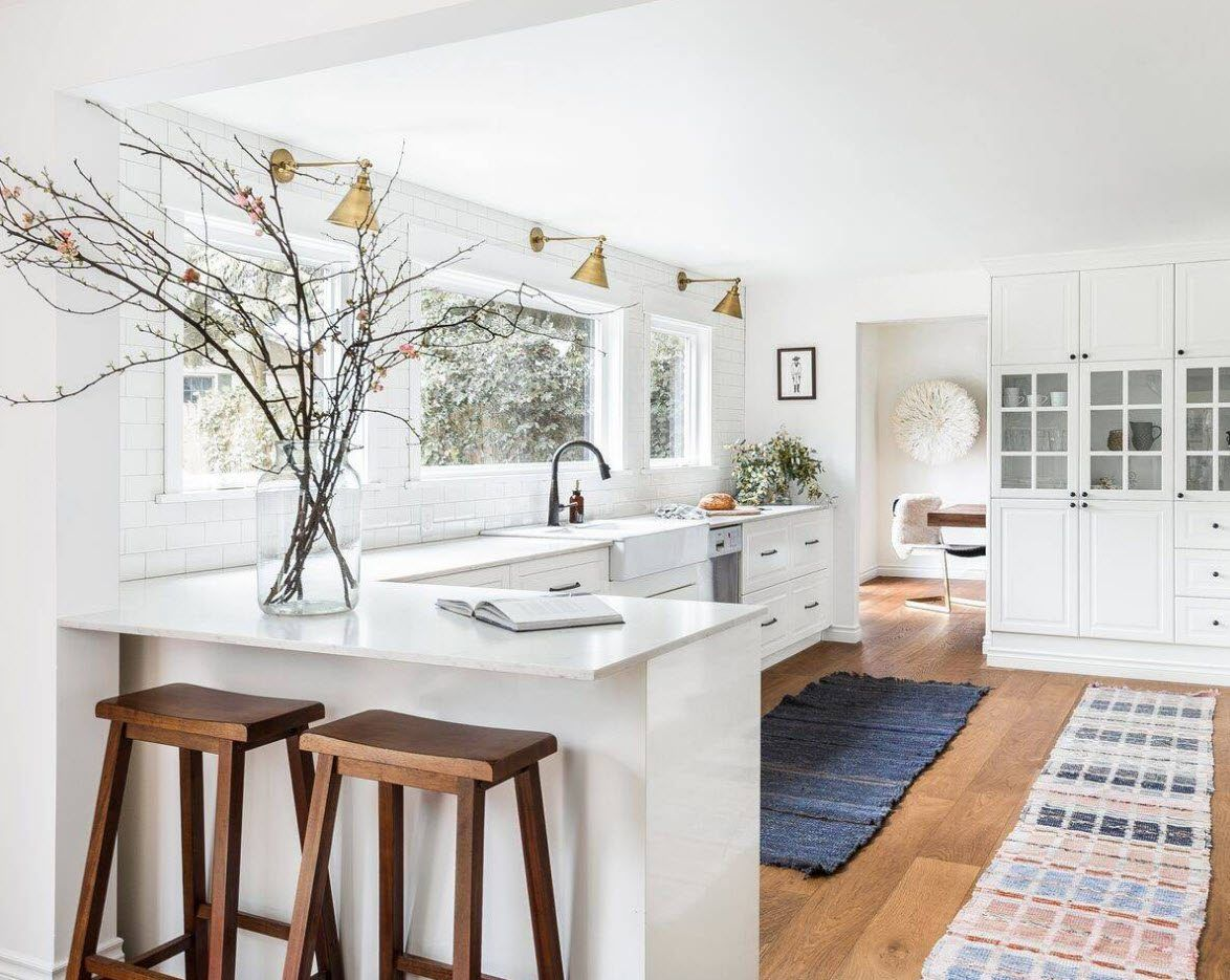 Absolutely white colored modern kitchen with functional windowsill and countertop with glossy coating