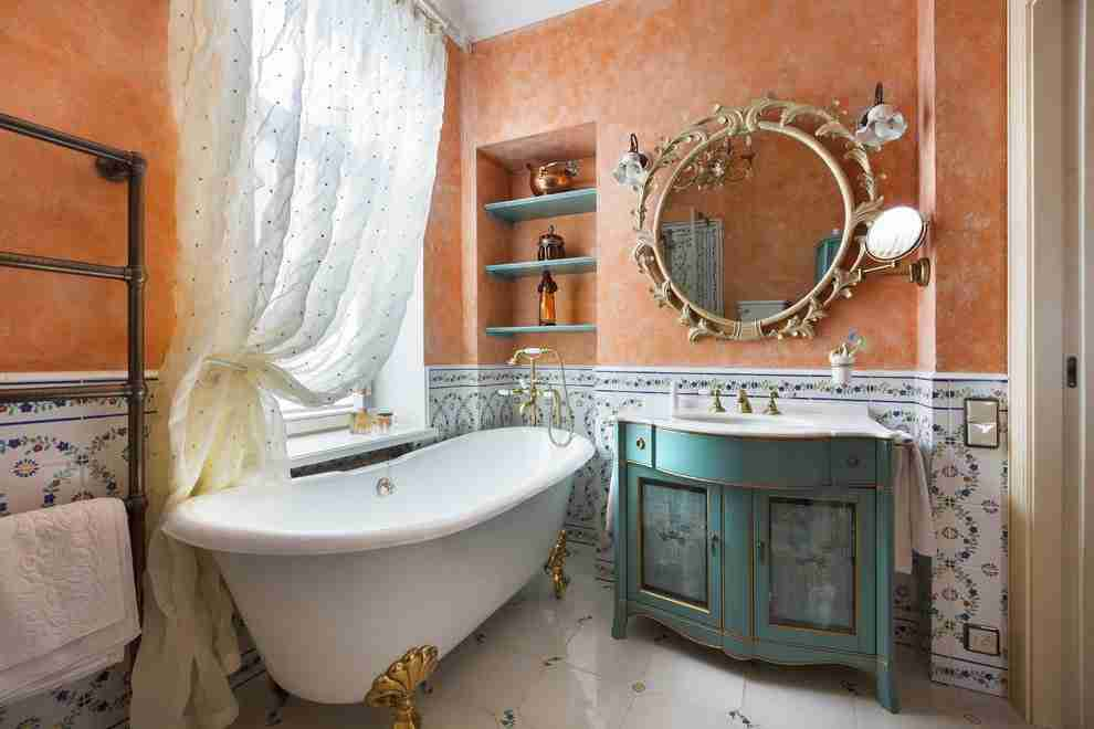 Bathroom Shelves: Fashionable Trends of Practical Interior Decoration. Vintage aged furniture and turquoise shelves in the recess above the white bathtub