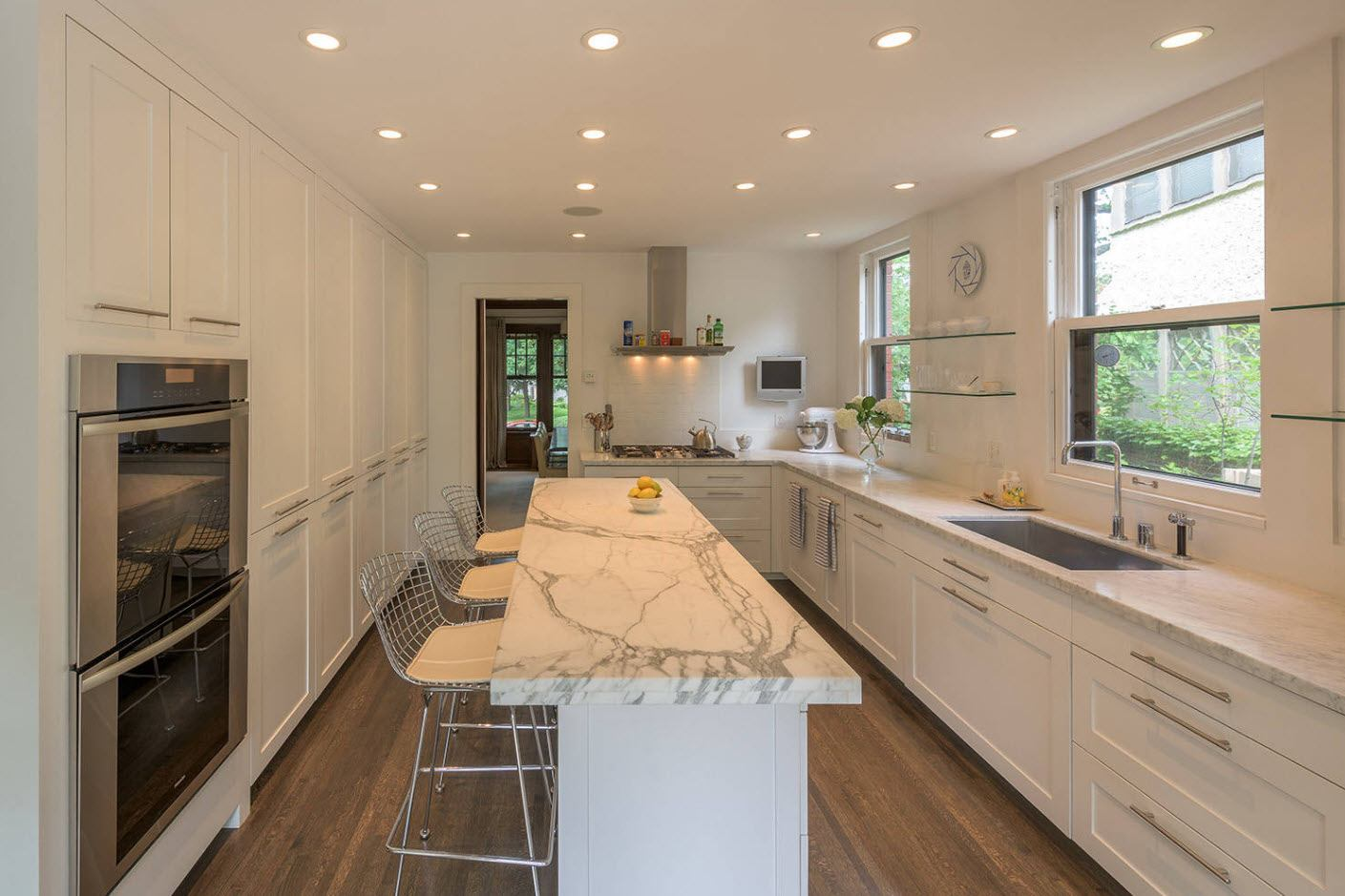 Intensive built-in lighting and marble imitating countertop of the island
