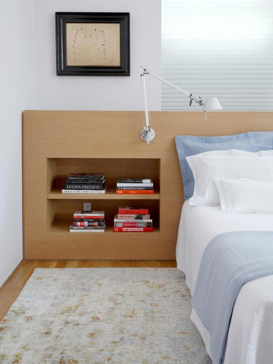 Shelves in the wooden cabinet in the headboard wall of the bedroom