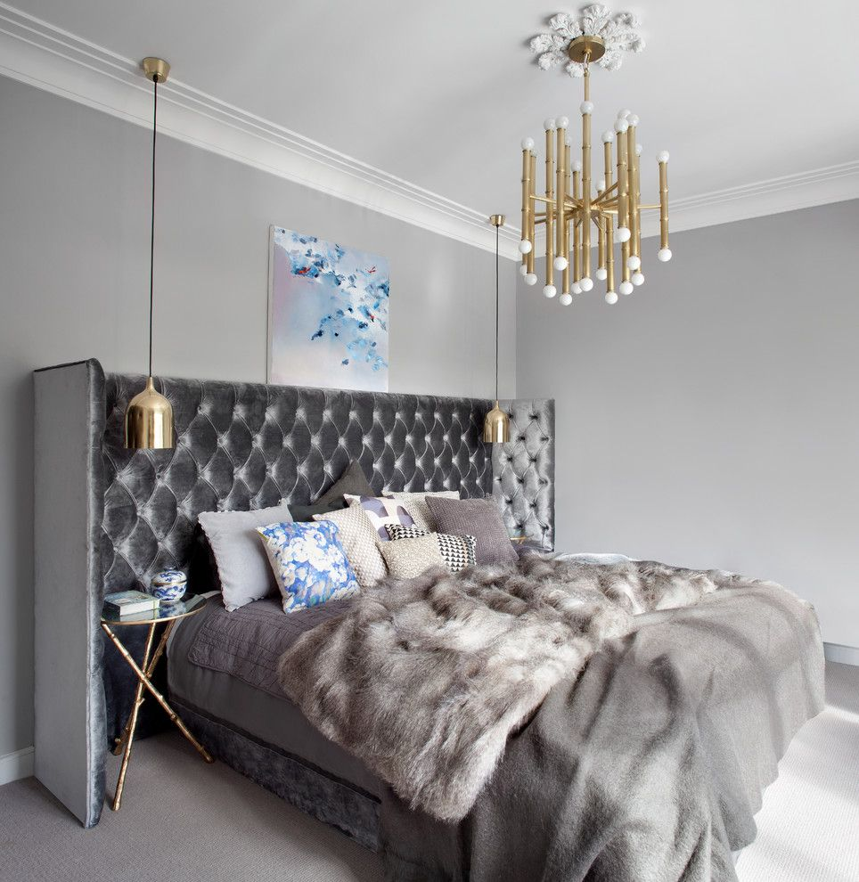 Large qulited gray headboard and gilded chandelier