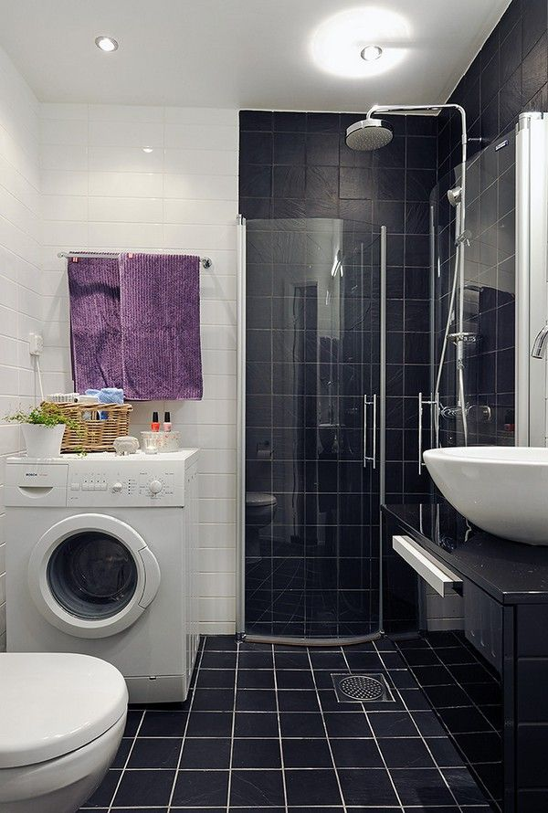 Wahing machine and other white elements in the bathroom with dark shower zone
