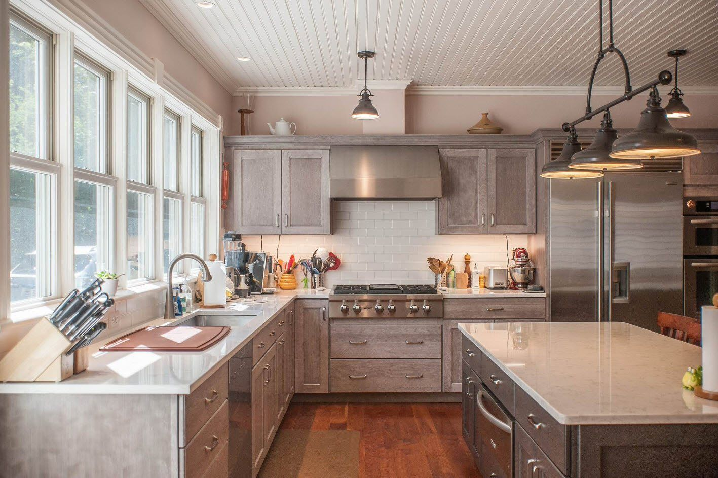 Gray kitchen cabinets and steel gray appliances contrasting with wooden floor