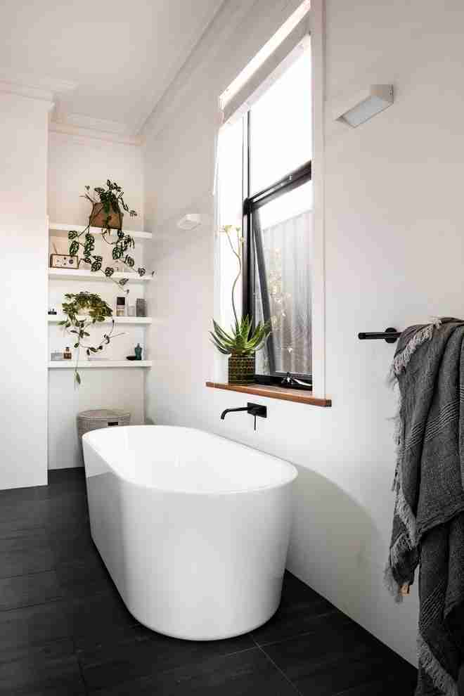 Absolutely white bathroom in Scandinavian style with oval stone bathtub