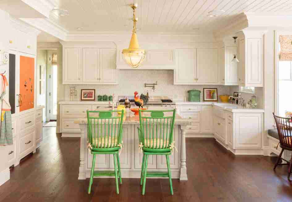 Green chairs in the light decorated kitchen with planked ceiling