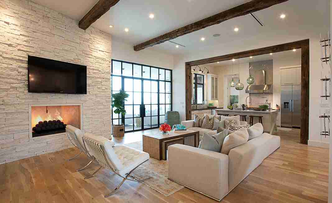 Artificial stone trimmed accent wall with TV-set in front of the white upholstered sofa