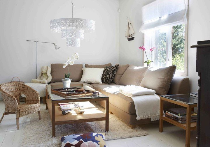 White decorated living room with the brown sofa and beige pillows