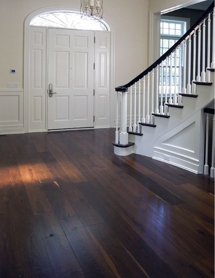 Tips for Keeping Your Hardwood Floors Clean. Dark wooden floor in the private house decorated in white