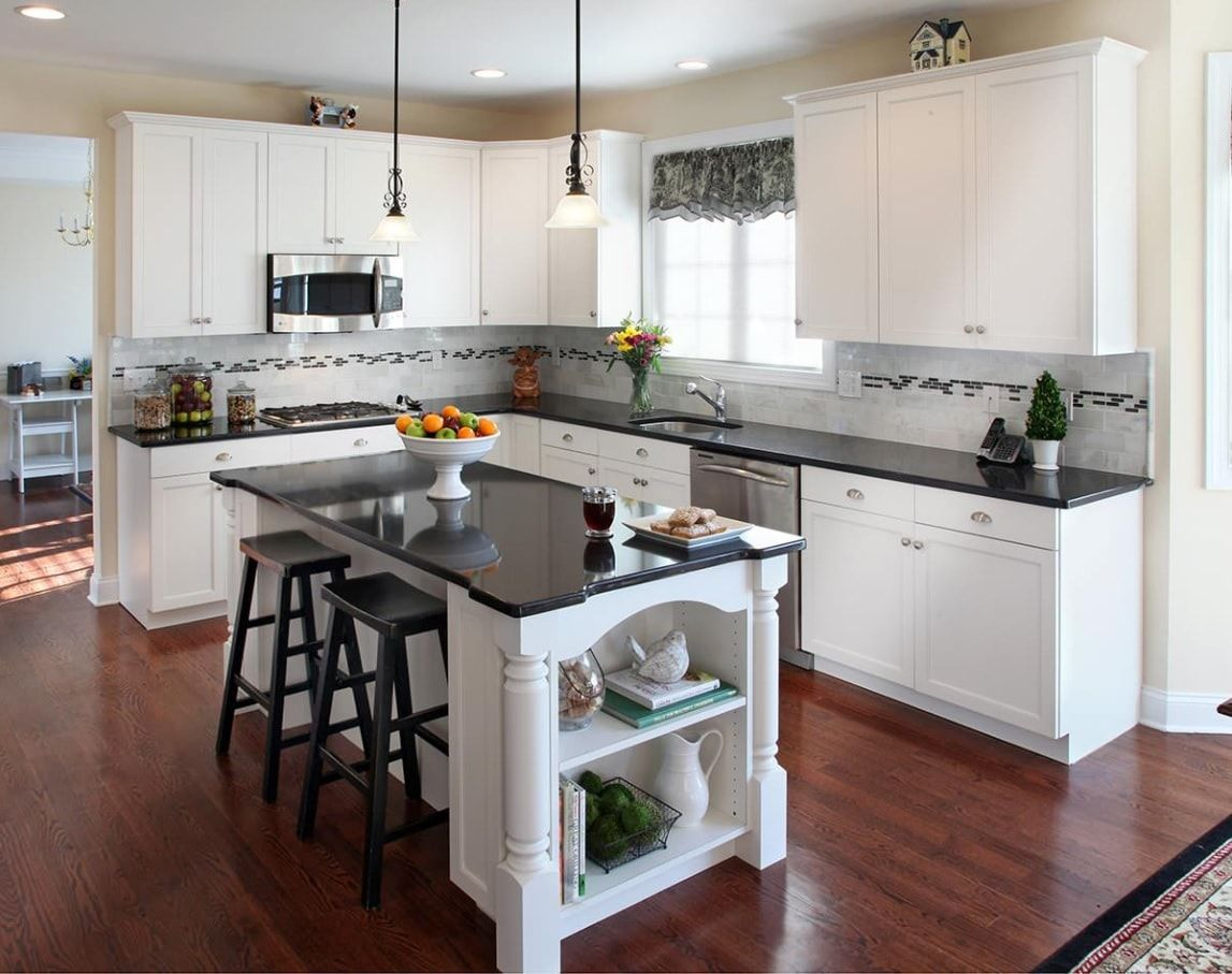 Things To Keep In Mind When Remodeling Your Kitchen. Dark stone glossy countertop and dining group around the island