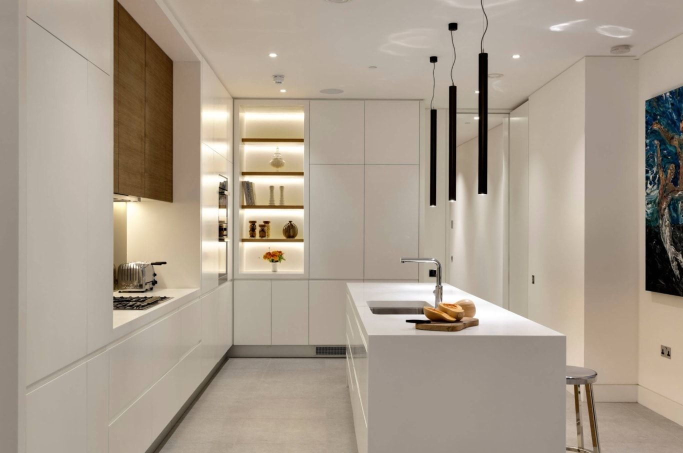 Small minimalistic hi-tech kitchen with LED-lighting in cupboards and large cooking island