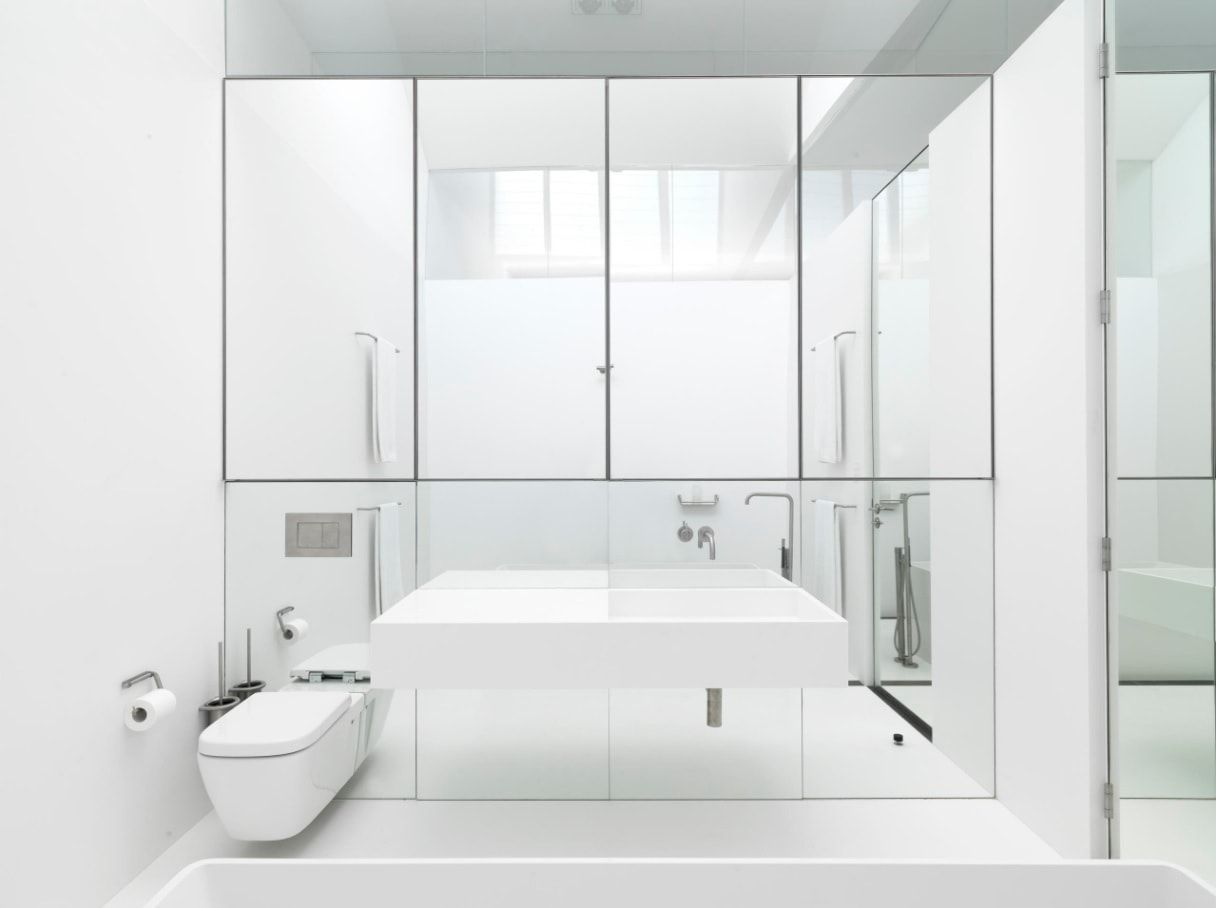 Futuristic design of the bathroom with suspended toilet and vanity, and mirror wall with cabinets shut