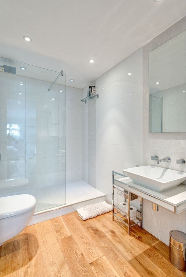 LIght decorated bathroom with glass trimmed shower zone and unexpected wooden flooring