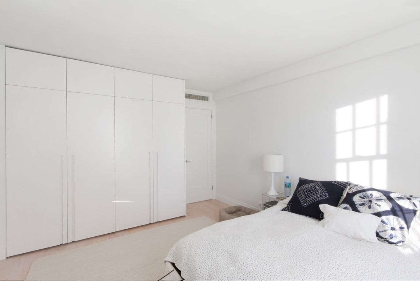Minimalist Interior Design Examples in Different Rooms. White matte surfaces in sterile white bedroom with wooden floor