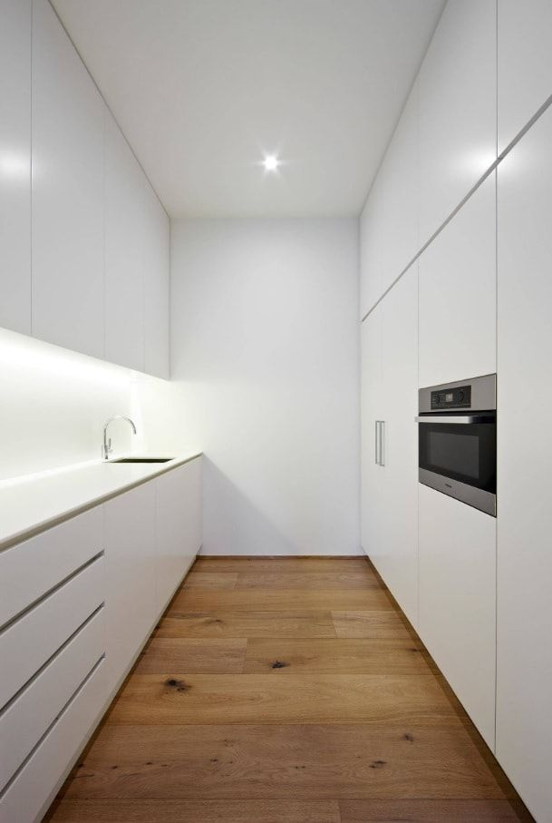 Minimalist Interior Design Examples in Different Rooms. Small galley kitchen with white matte facades and laminated floor
