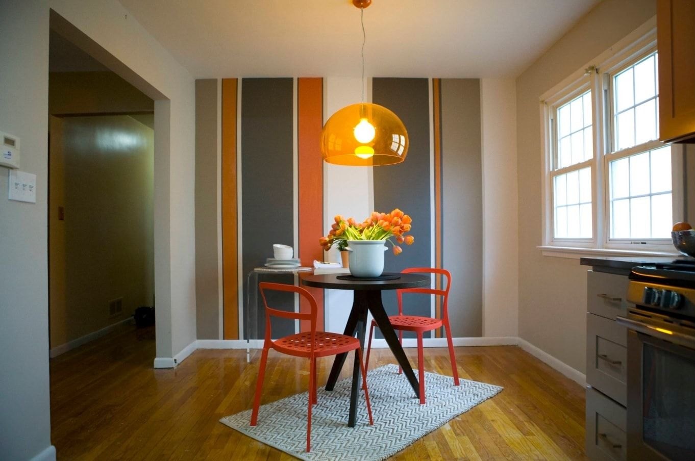 Simple but original design of the dining room with orange chairs and colorful stripes on the accent wall