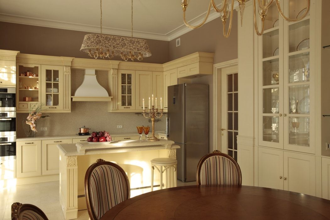 Italian Dining Room & Kitchen Combined in One Space. Dining zone with round wooden table and overall ivory color set of the room
