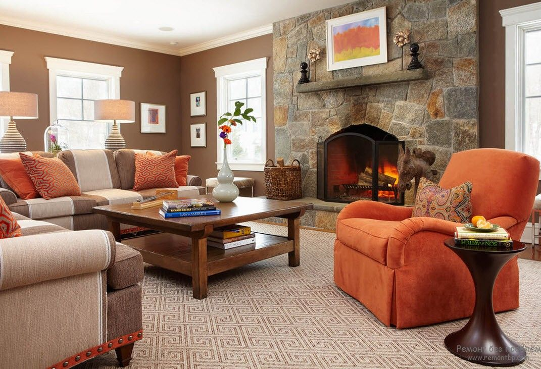 Greek Interior Design Style: Antiquity in Your Home. Stone trimmed fireplace in the beige decorated room with orange upholstered armchairs