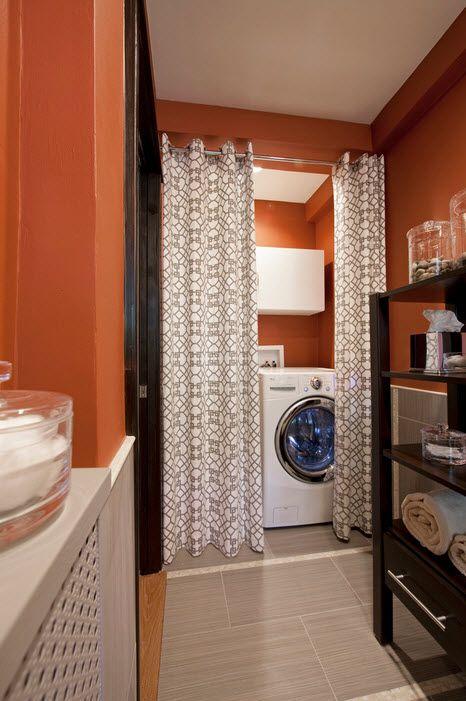 The red colored walls in the bathroom with appliances hidden behind the curtain