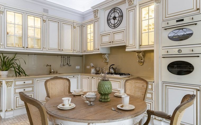 Italian Dining Room & Kitchen Combined in One Space. Carved wooden kitchen set and round wooden table