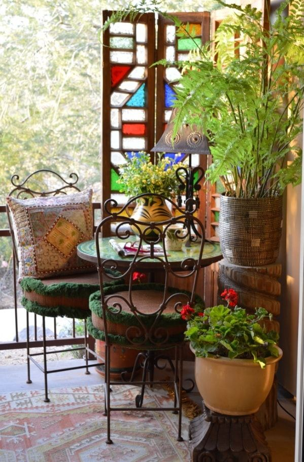 Top 10 Small Apartment Patio Ideas with Photos. Wrought iron furniture and the round table at the relaxing zone with flowers and plants