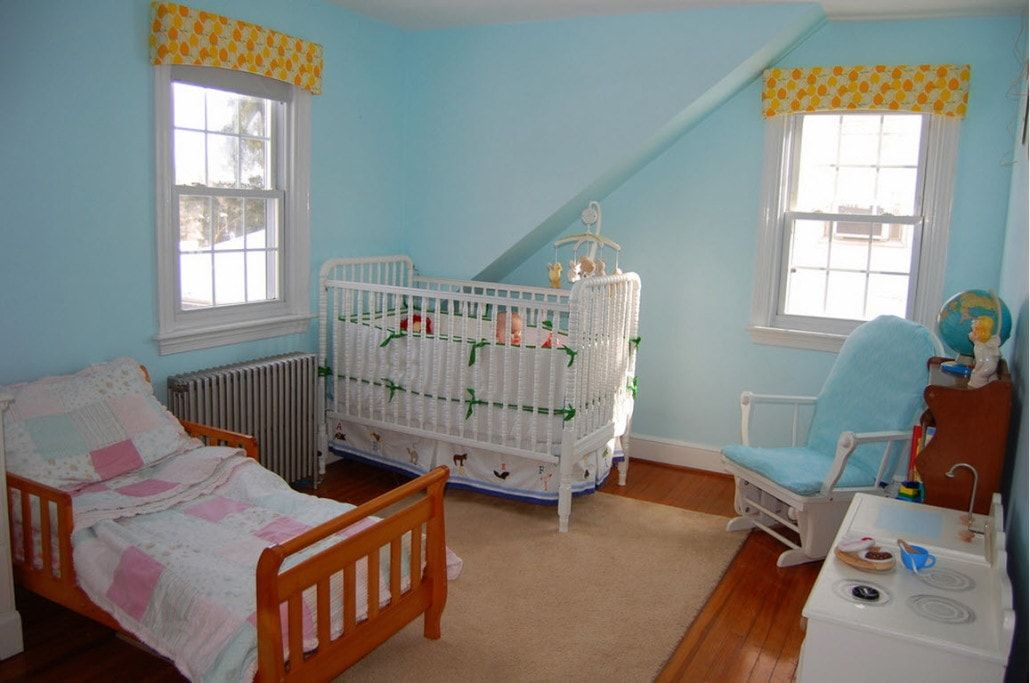 Blue colored kids' room with the small bed and a separate crib
