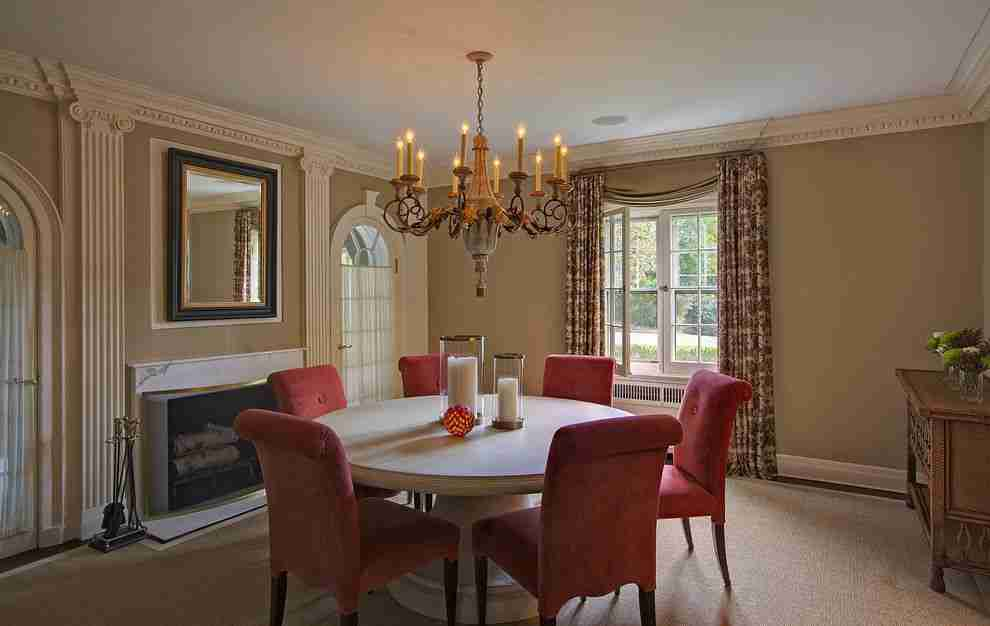 Pilasters in the Interior - Indispensable Element of Luxurious Design. Typical classic interior with round table, red chairs and chandelier