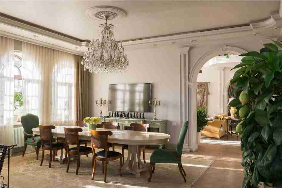 Pilasters in the Interior - Indispensable Element of Luxurious Design. Gray colored royal Classic dining room with large crystal chandelier