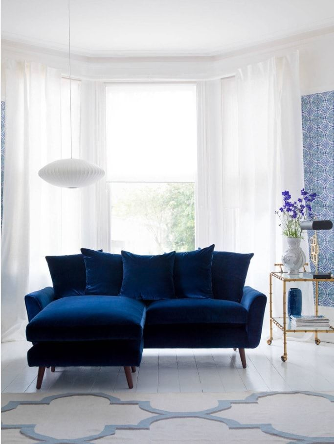10 Top Secret Decorating Tips for Selling Your Home. Blue angular sofa with ottoman in the minimalistic room with white tulle
