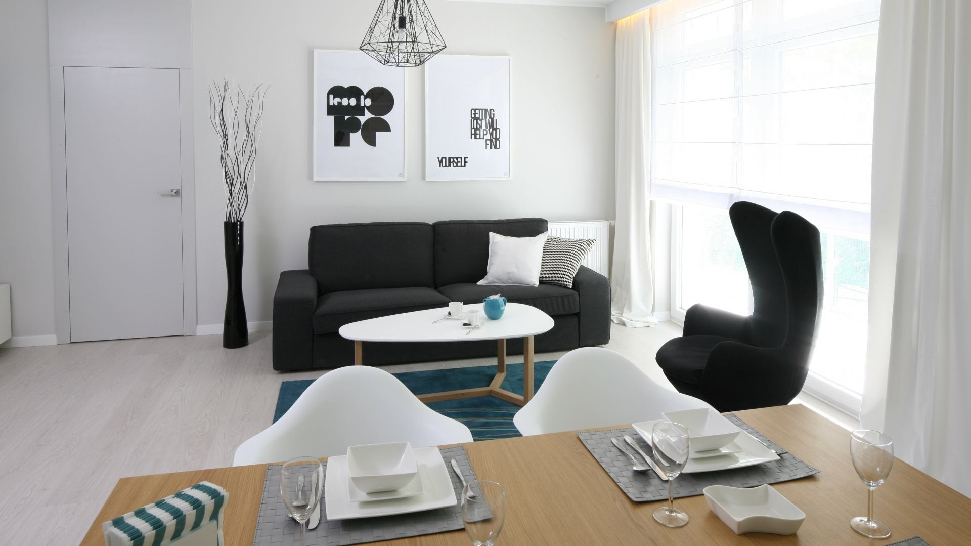 Black Sofa: Elegant and Original Design for Flawless Interior. White Scandi styled oval coffee table in the white colored modern living