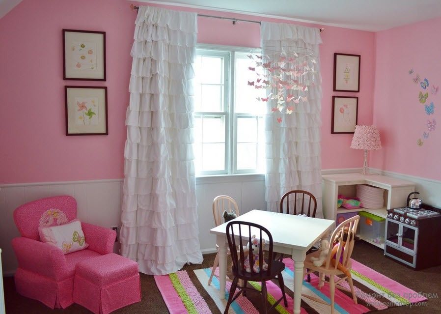 Curtains in the Interior of the Children's Room. White tulle in the window of the pink painted room with striped rug