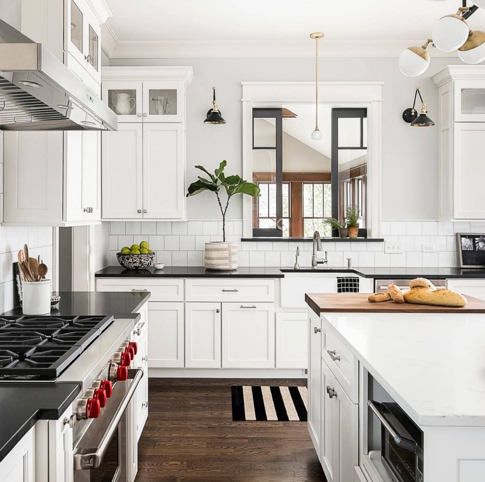 Contrast of absolutely white kitchen set and dark laminated floor