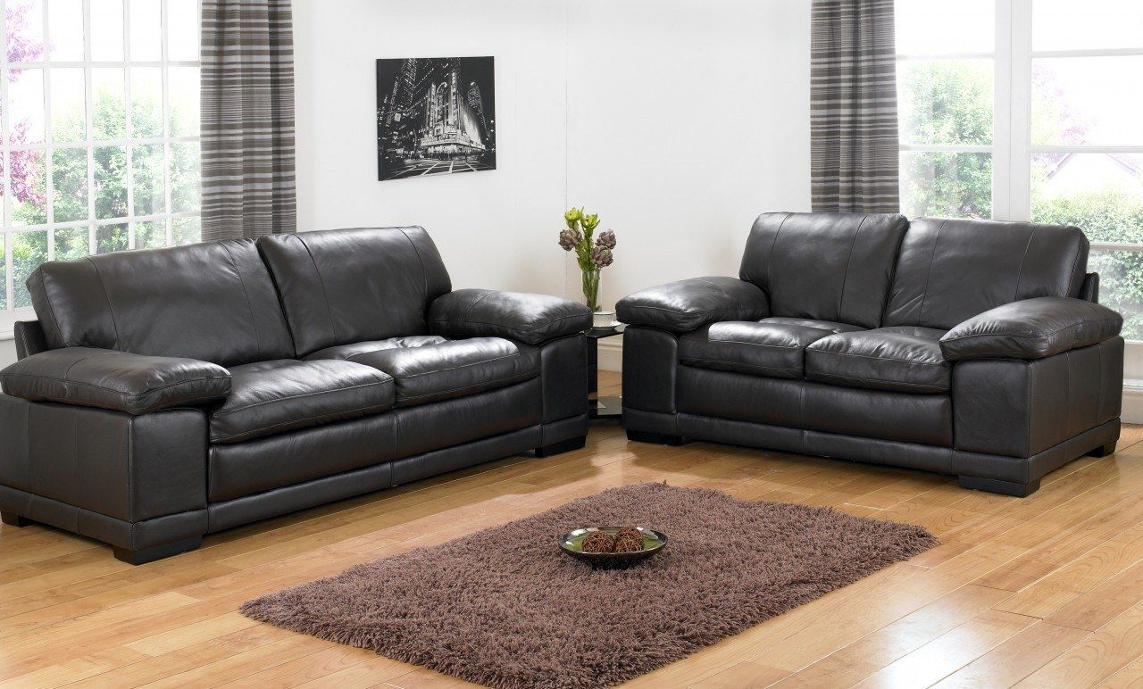two black sofas in the classci designed room with white walls