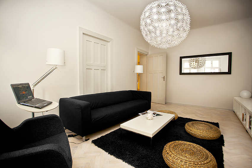 Black Sofa: Elegant and Original Design for Flawless Interior. Plain sofa and white coffee table at the black carpet and large chandelier for white painted room
