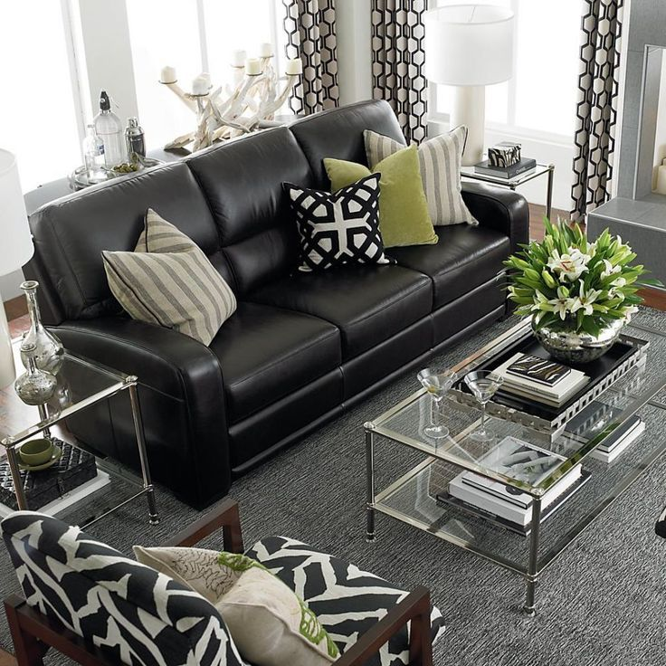 Steel framed furniture with glass inserts and black sofa in the light living room