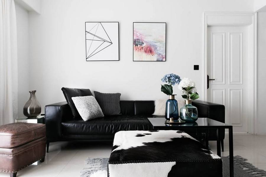 White modern designed room with abstract paintings and black furniture