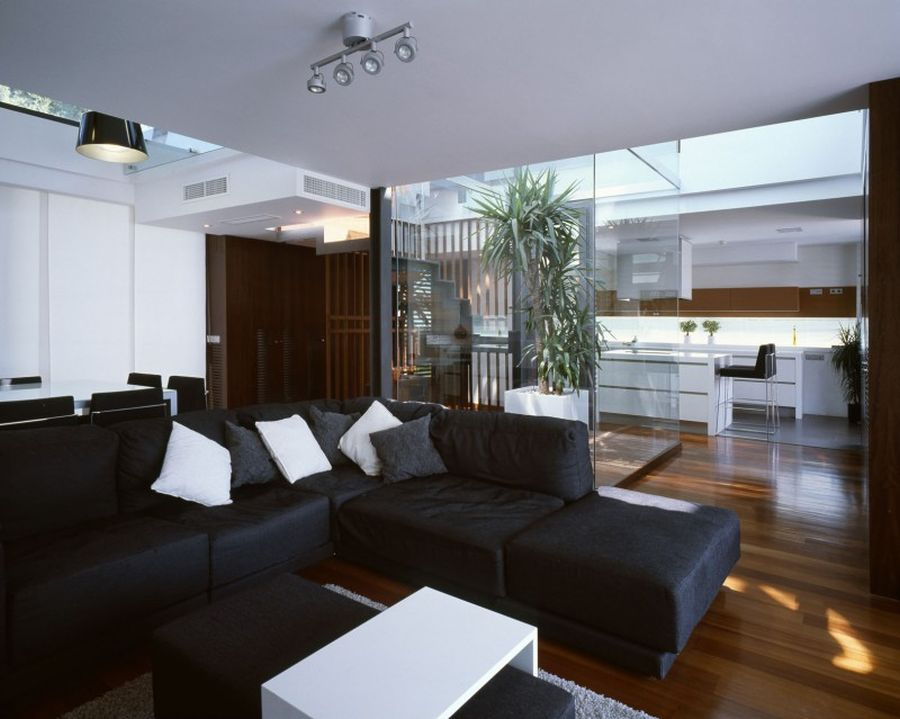 Black sofa in the single-storey cottage with modern interior design