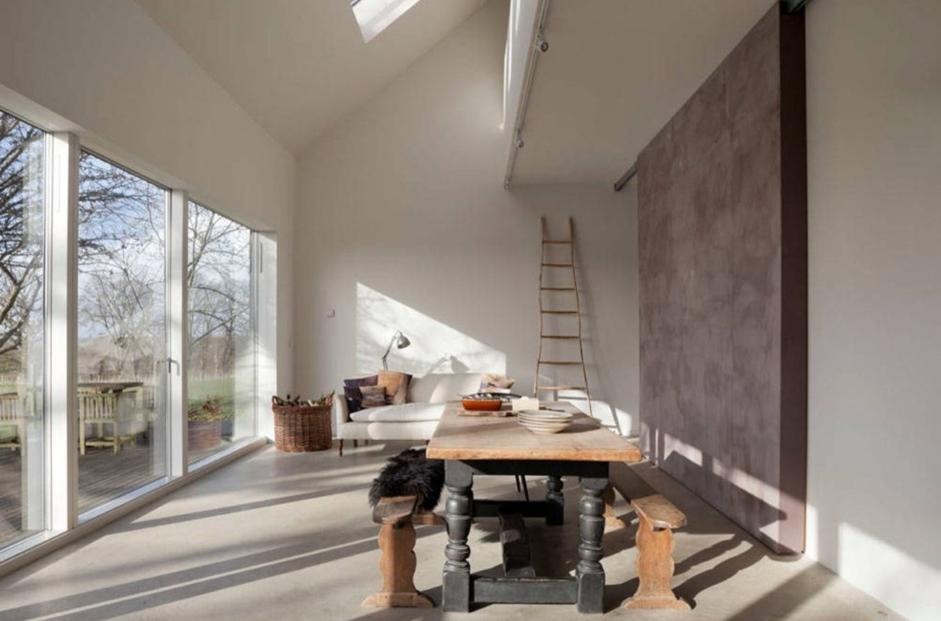 Faux Concrete Wall Paint: Modern and Original Finishing. Cottage in light tones with pronounced purple colored accent wall