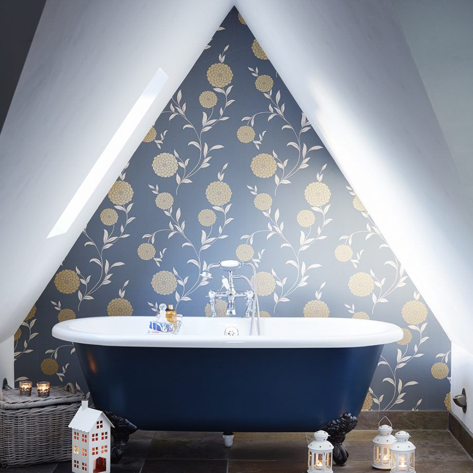 Triangle gable wall with floral themed wallpaper and the blue bathtub