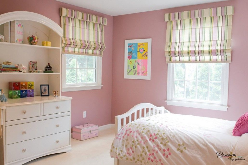 Dark pink wall color and pastel Roman blinds in the children's room with white furniture