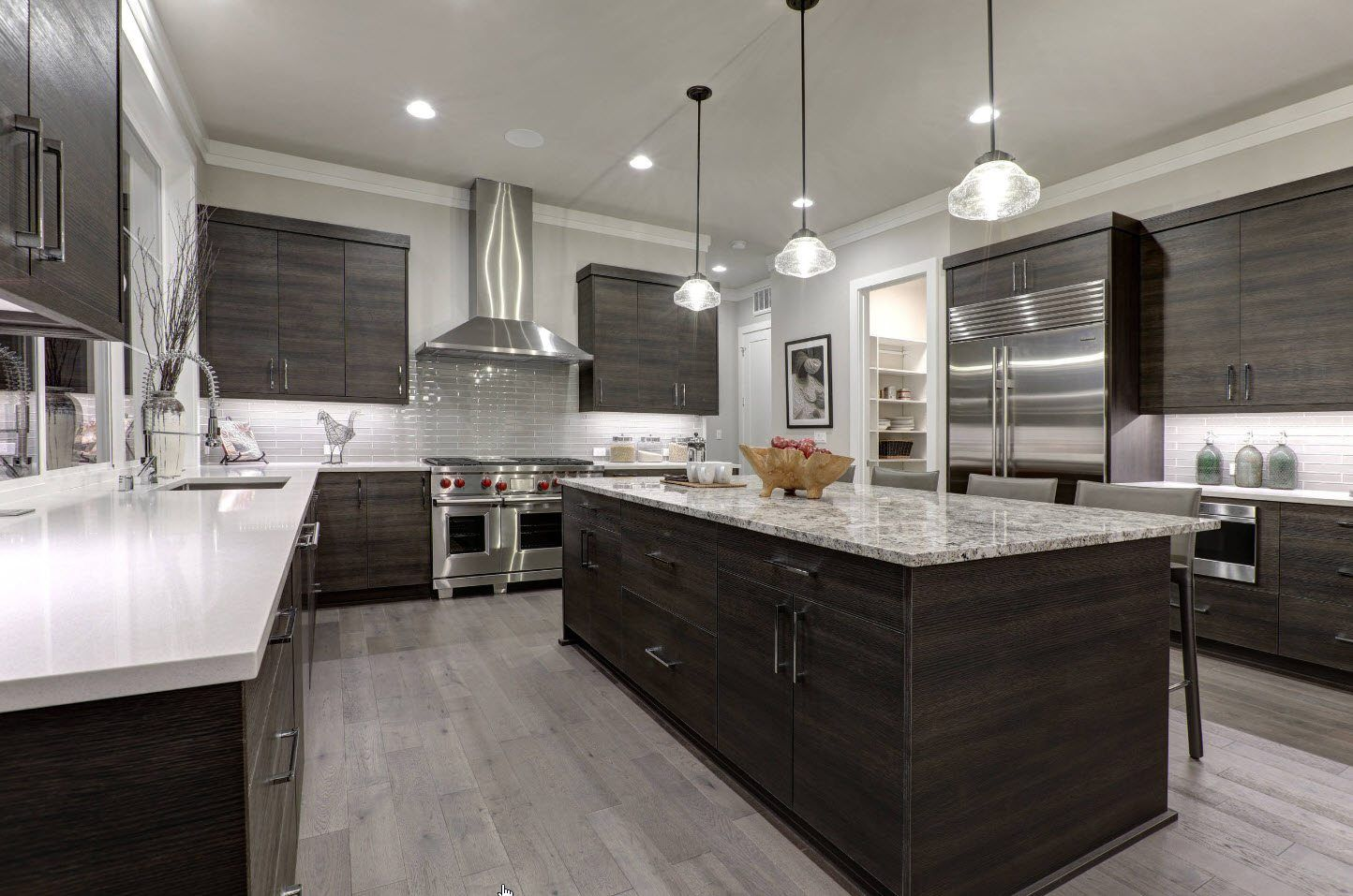 Black wooden kitchen island in the large room with dark furniture facades
