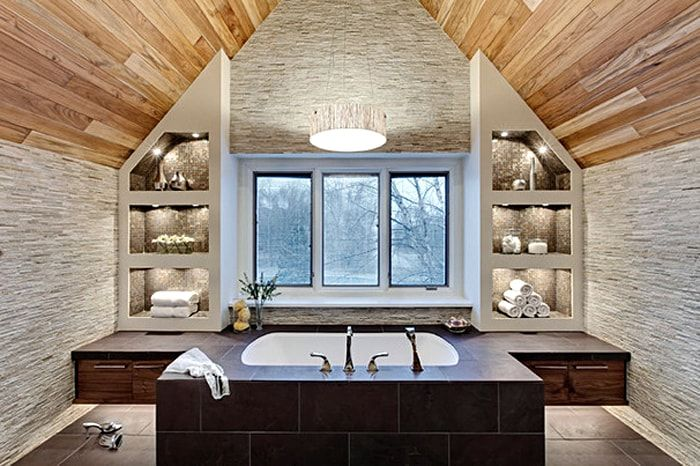 Royal attic bathroom design with large window and central placement of bathtub with many controls and taps