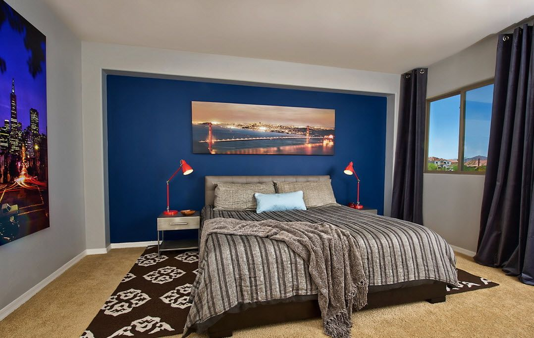 Blue painted accent wall in the Classic bedroom with dark gray bedding