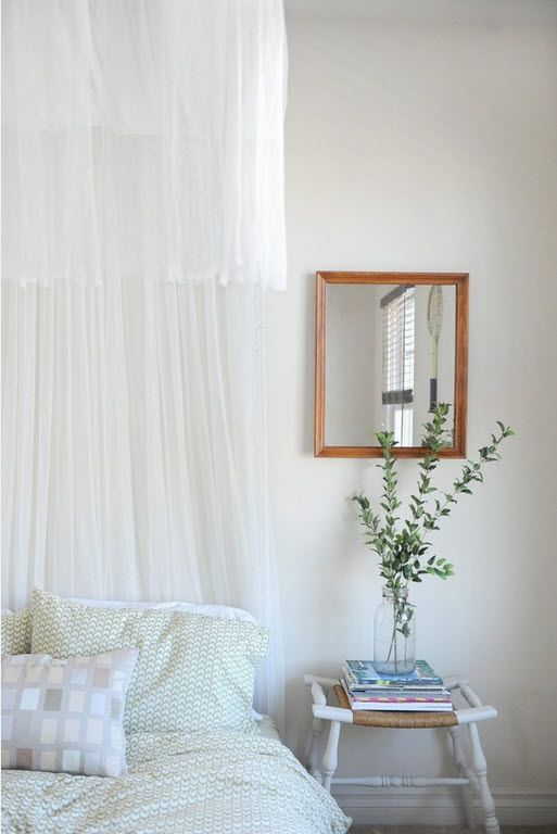Cozy casual white bedroom with tulle and wooden framed mirror
