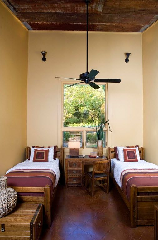 Beige colored walls and black fan in the room for two