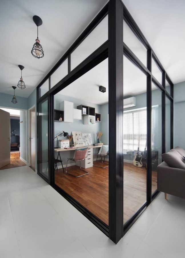 Unusual design of study room right among the open space apartment framed with black steel rails and glass
