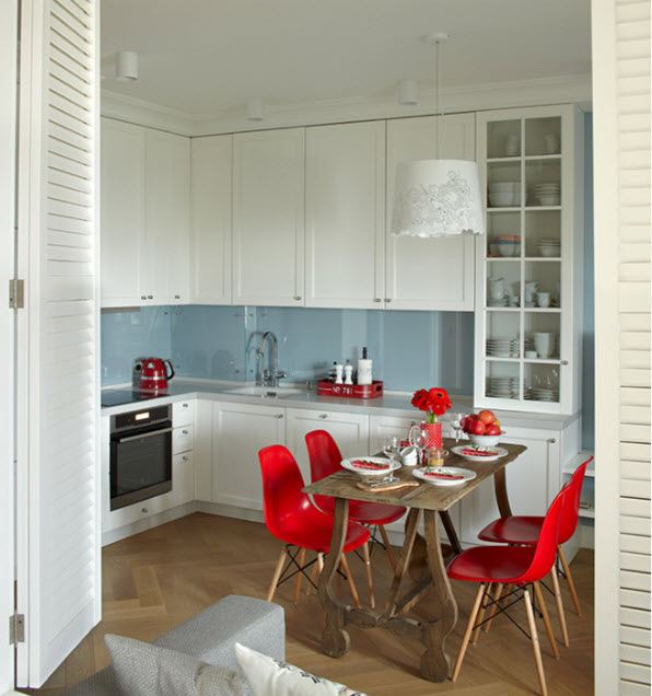 Neat restrained kitchen interior with red chairs at the dining zone