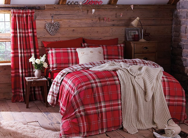 Ethnic rustical styled bedroom with wooden headboard and red checkered blanket