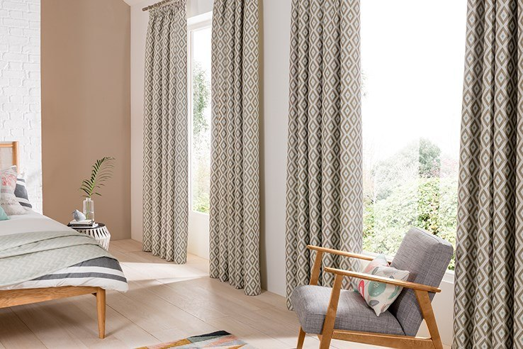 Heavy gray curtains and large windows for contemporary furnished bedroom